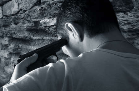 death head holding: The man with a pistol on a background of a brick wall
