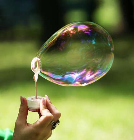 bulles de savon: La jeune fille fait grande bulle de savon dans parc