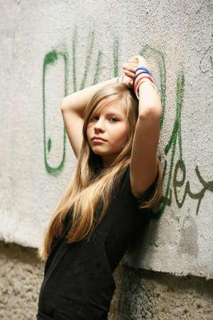 La ragazza - adolescente su uno sfondo di un muro Archivio Fotografico - 8420731