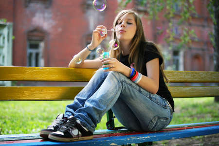 The young girl makes soap bubble photo