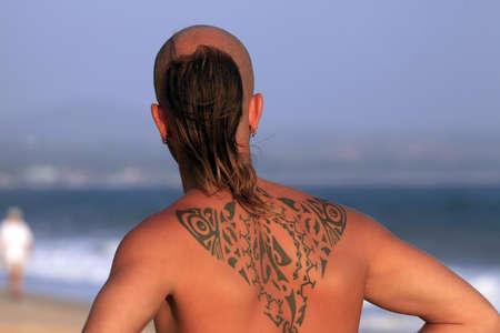 sexy tattoo: El joven con un hermoso tatuaje en una costa del Oc�ano Foto de archivo