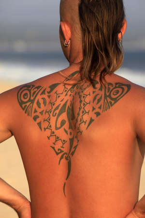 The young man with a beautiful tattoo on a coast of ocean photo