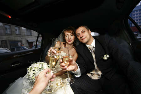Newly-married couple with glasses of champagne in the automobile photo
