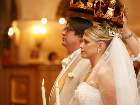 The groom and the bride with candles. Wedding ceremony in church photo