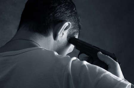 Der Mann mit einer Pistole auf einem Hintergrund von einer Ziegelmauer Lizenzfreie Bilder