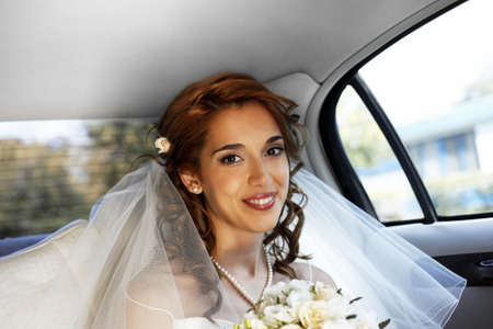 getting married: The beautiful smiling bride in the automobile