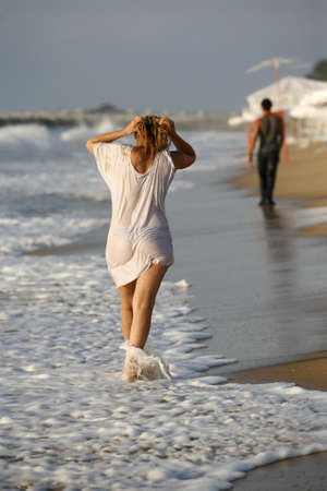 The girl in a wet shirt and the man at coastline photo