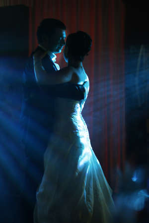 The first dance of the groom and the bride in blue beams                          Stock Photo