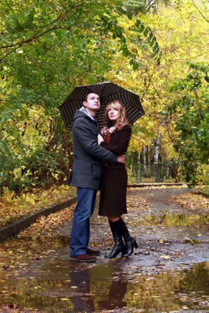 Couple in autumn park under a umbrella photo