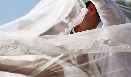 getting married: The groom and the bride kiss having closed by a veil