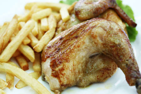 Roasted chicken on a plate with fried potato photo