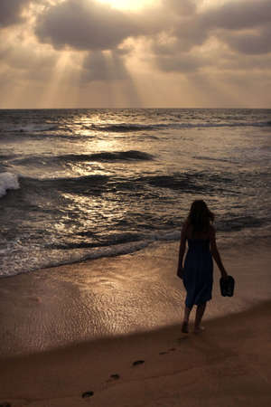 The lonely girl on a beach on sunset Stock Photo - 11395614