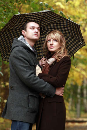 Couple in autumn park under a umbrella photo