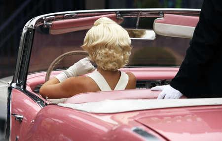 Blond girl model like Marilyn Monroe in car Stock Photo