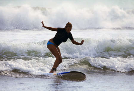 Adult woman - the surfer in ocean. Bali. Indonesia