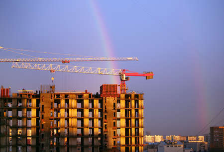 overhead crane: The elevating crane of construction on a background of the dark blue sky and a rainbow Stock Photo