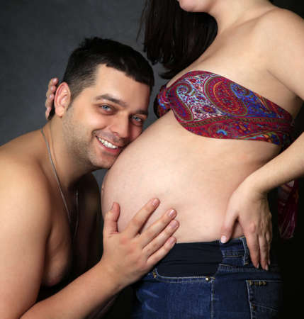 Portrait of happy daddy and his pregnant wife photo