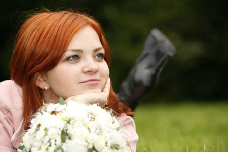cautious: The nice girl with a bouquet in a grass
