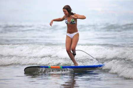 Junges M�dchen - der Surfer im Ozean. Bali. Indonesien