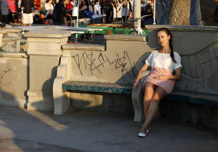 Beautiful girl has a rest on a bench  Venice Beach in California photo