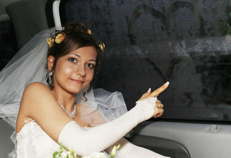 The bride in the automobile draws on glass Stock Photo - 13419629