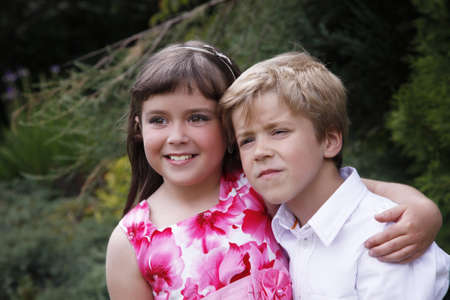arms around: Brother and sister outdoors smiling Stock Photo