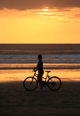 The woman with a bicycle on a coast of ocean photo