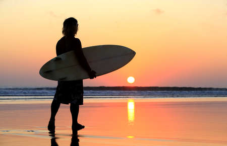 Silhouette of surfer at red sunset  Kuta beach  Bali photo