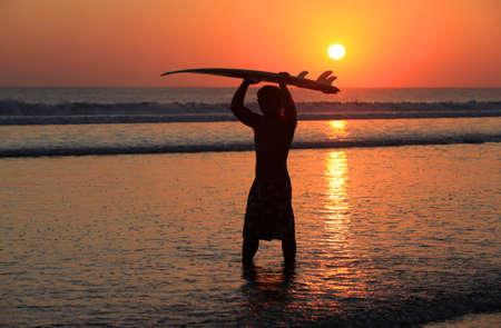 passtime: Silhouettes of surfer at red sunset  Kuta beach  Bali Stock Photo