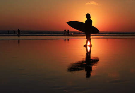 Silhouettes of surfer at red sunset  Kuta beach  Bali photo