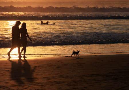 parejas caminando: Pareja con perro en la puesta del sol. Costa del Océano Índico
