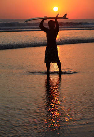 Silhouette of surfer at red sunset. Kuta beach. Bali photo