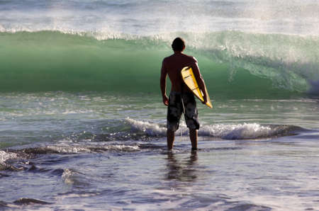 Man-Surfer mit Brett auf einer K�ste. Bali. Indonesien