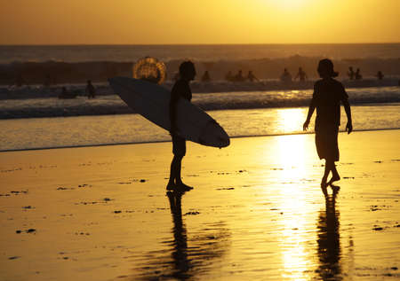 Silhouette of surfers in golden sunset light  Bali Stock Photo - 15134120