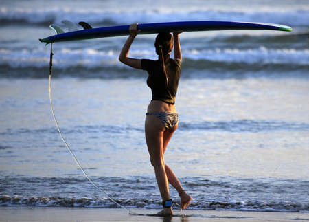Woman-surfer with board on a coastline. Bali. Indonesia photo