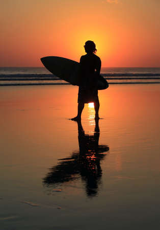 Silhouette of surfer with a board on a sunset