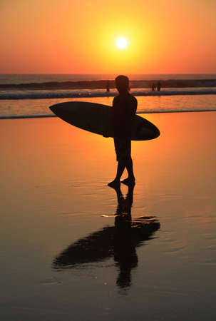 Silhouette of surfer with a board on a sunset photo