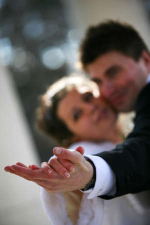 Dance of a newly-married couple. Hands in a zone of sharpness, the rest is dim photo