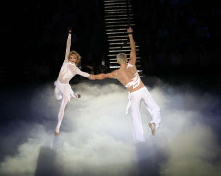 Two air acrobats carry out exercise on a circus ring