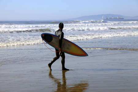 Surfer on a coastline. Ocean Beach, San Franciso, CA photo