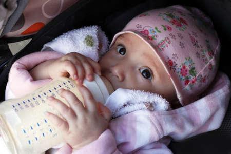 The little girl eats porridge from a bottle photo