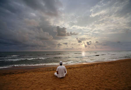 Guy meditating at sunset sitting on coastline  photo