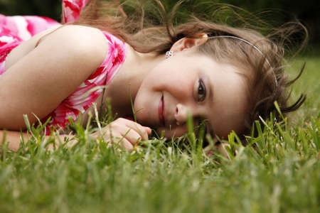 Cute little girl on the meadow in spring day photo