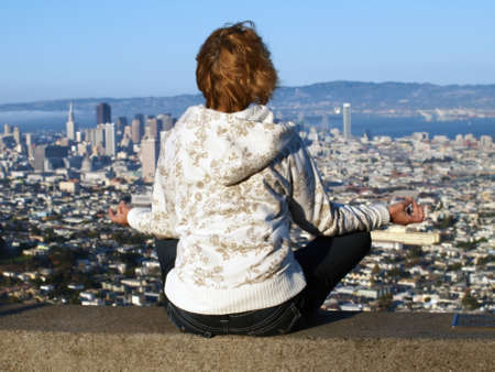meditates:  The woman meditates  on a background of Twin Peaks, San Francisco.