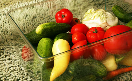 assorted vegetables in a plastic box on a green background photo
