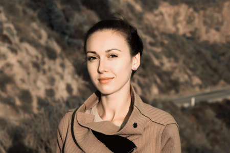 Portrait of a beautiful brunette on a background of mountain road photo