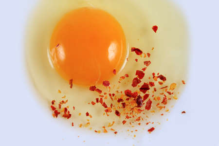 Egg yolk with spices closeup on white background photo
