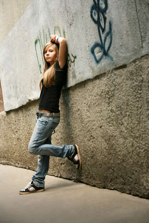 runaway: The girl - teenager on a background of a wall