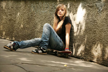 The girl with skateboard sitting against a wall