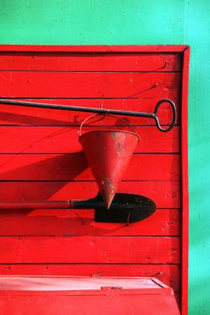 breakage: cubo, una pala, una rotura en contra de un cobertizo de madera rojo viejo
